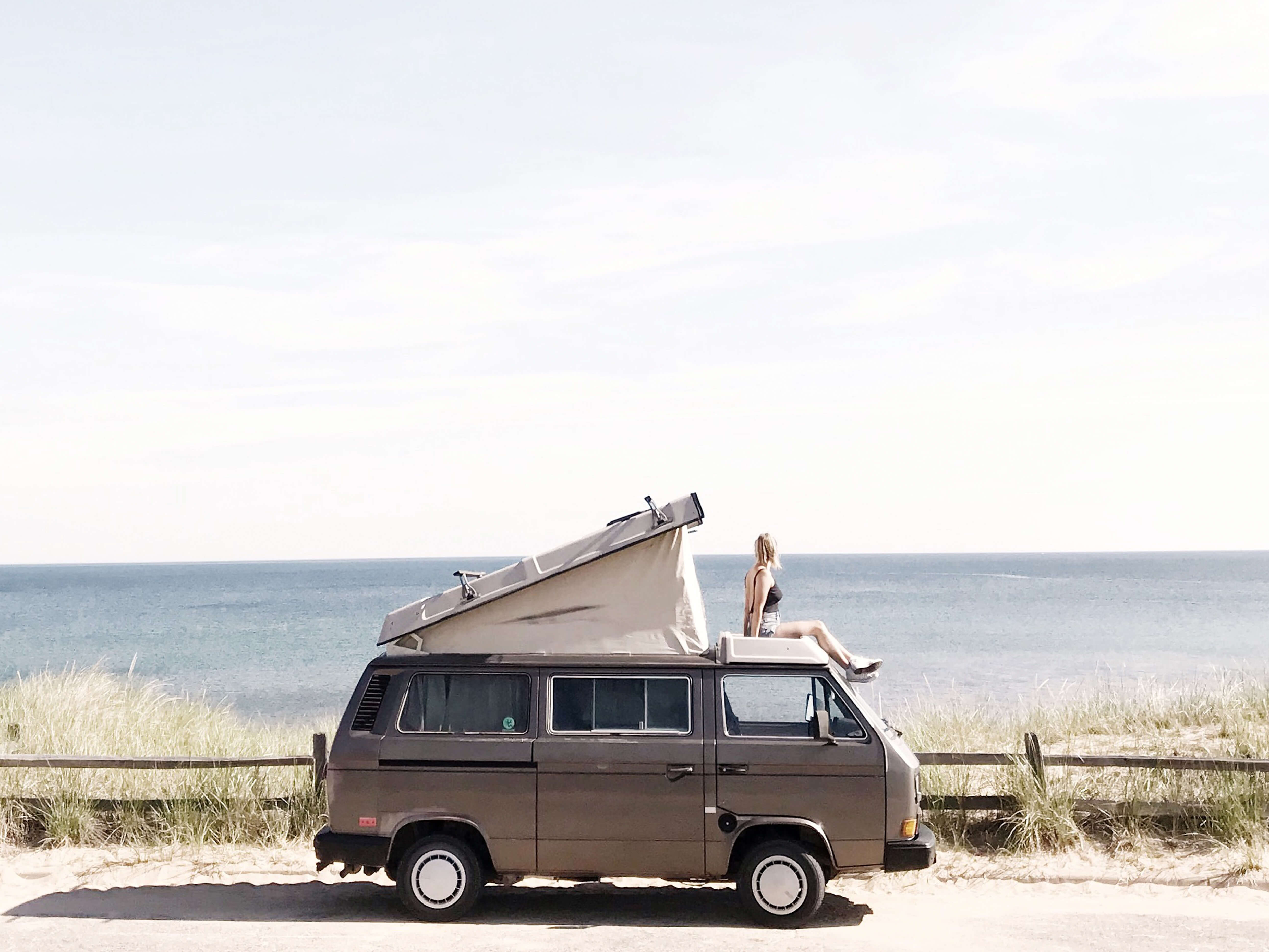 Woman sitting atop camper van