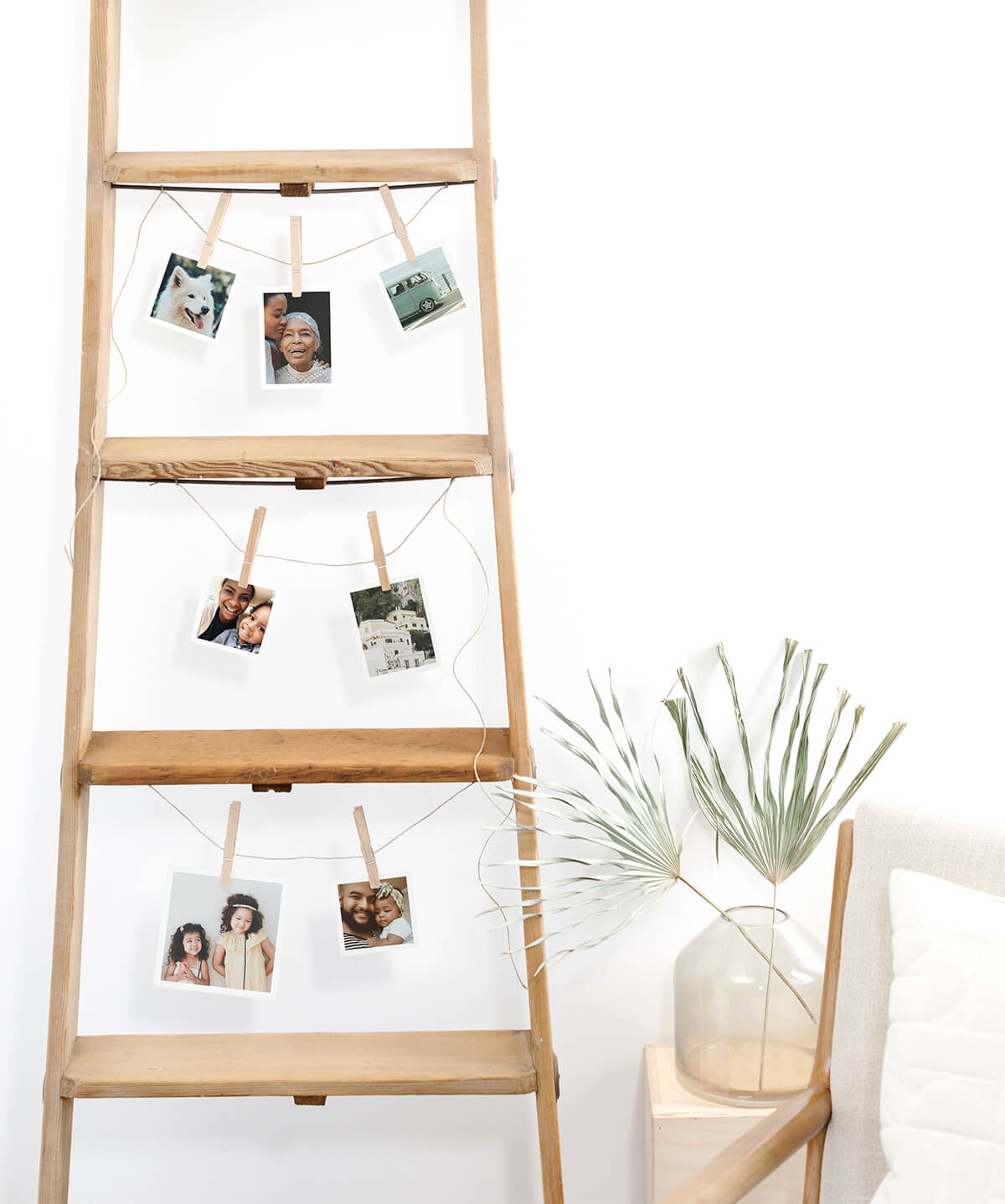 Photo prints hanging from rungs of wooden ladder