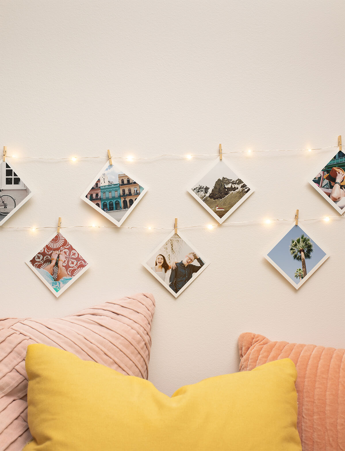 Diagonally rotated square prints hanging from lit up string lights