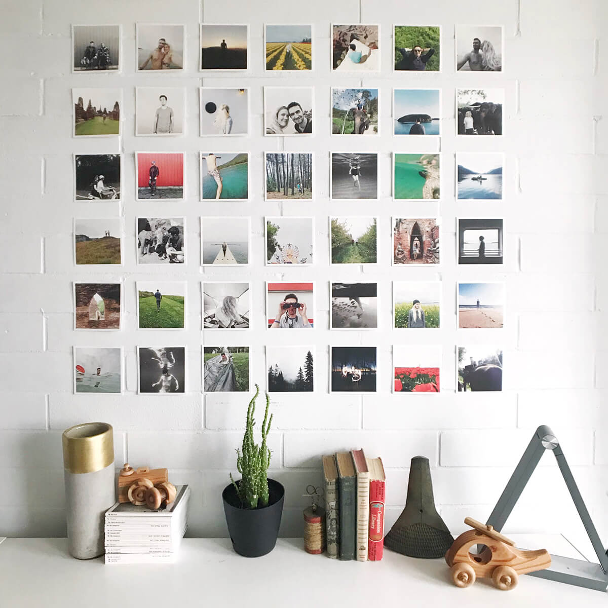 Square grid arrangement of photo prints on wall