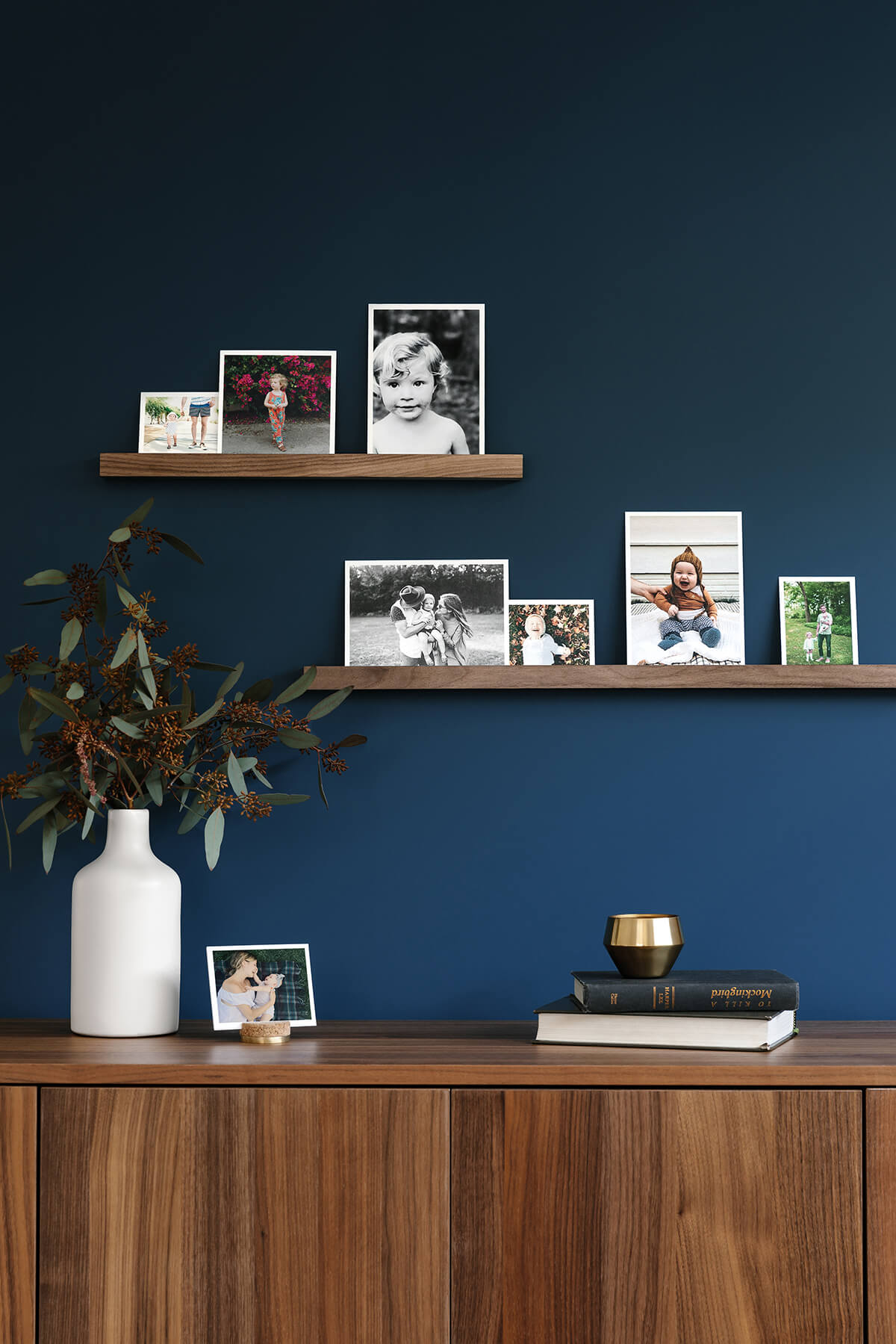 Prints arranged on a wooden photo ledge