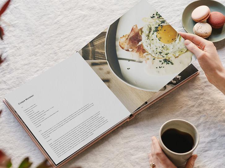 Hands flipping through cookbook created from Layflat Photo Album