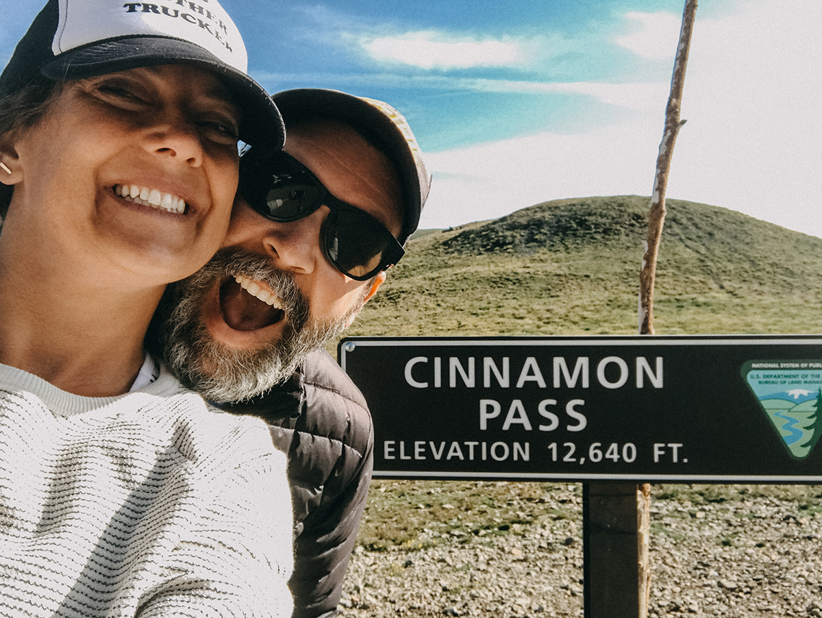 Liz young with husband by Cinnamon Pass sign