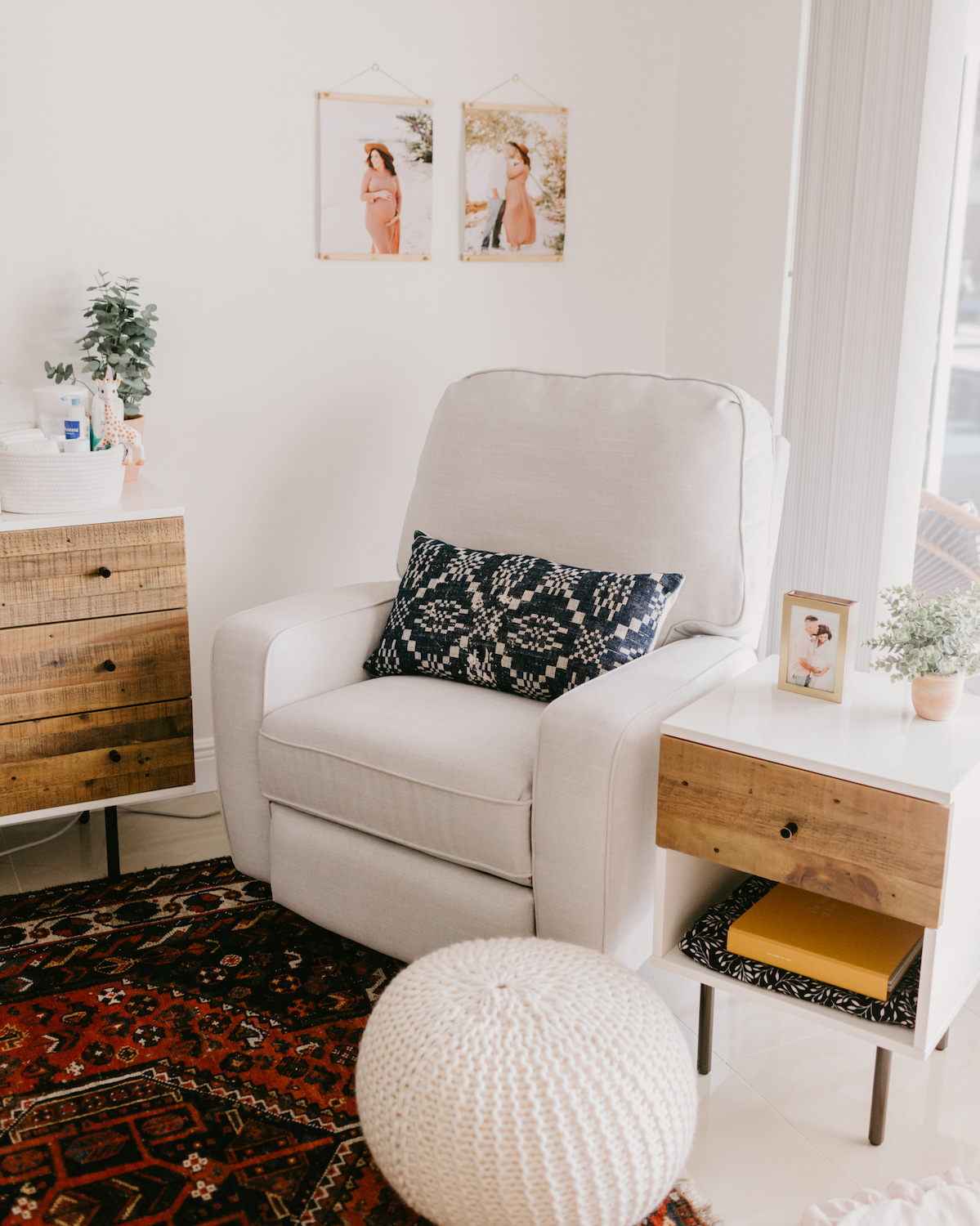 Couch, side table, and pouf with nursery wall decor in background