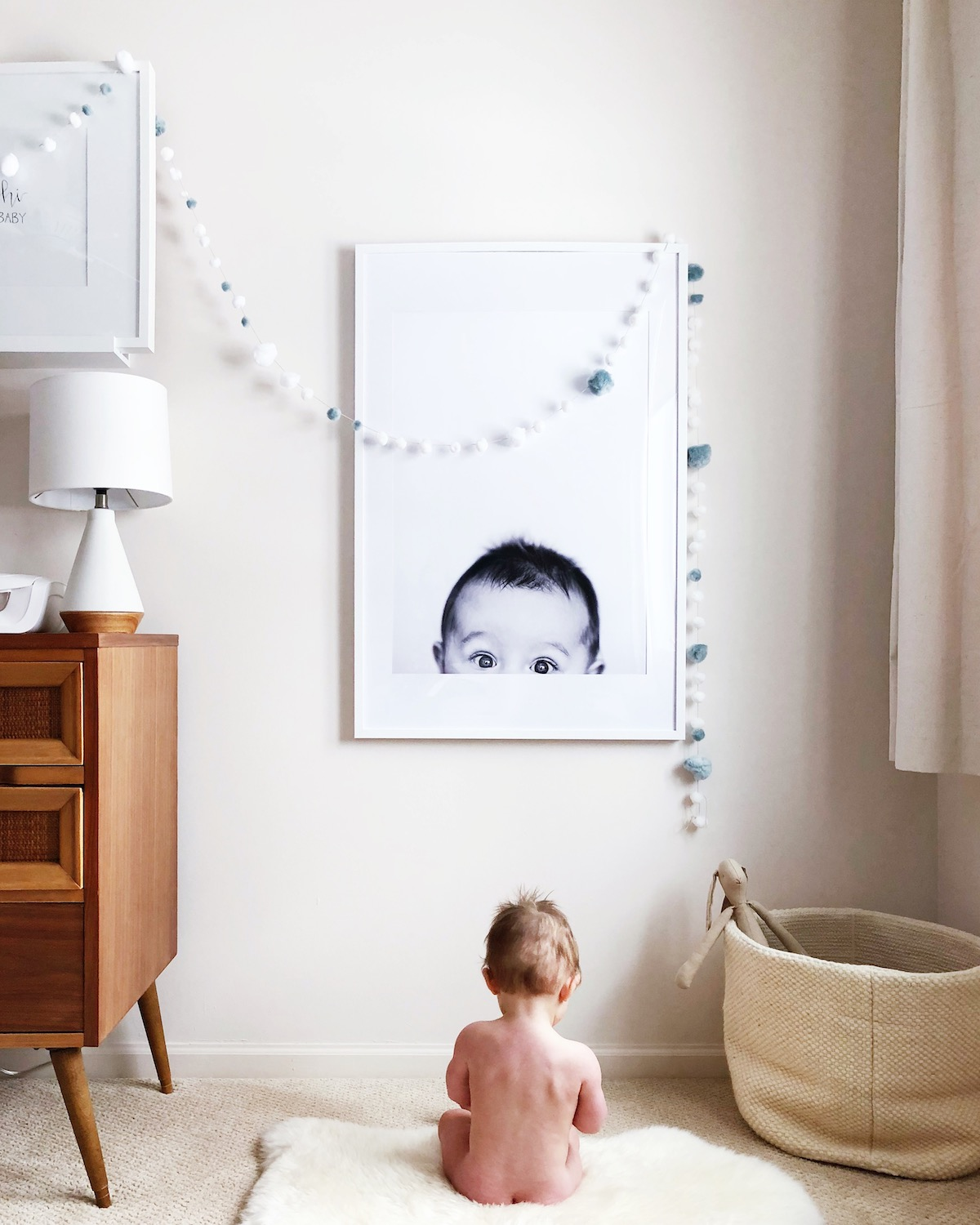 Baby photo enlarged and framed on wall in nursery
