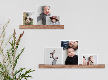 Floating shelves featuring baby photos in a nursery