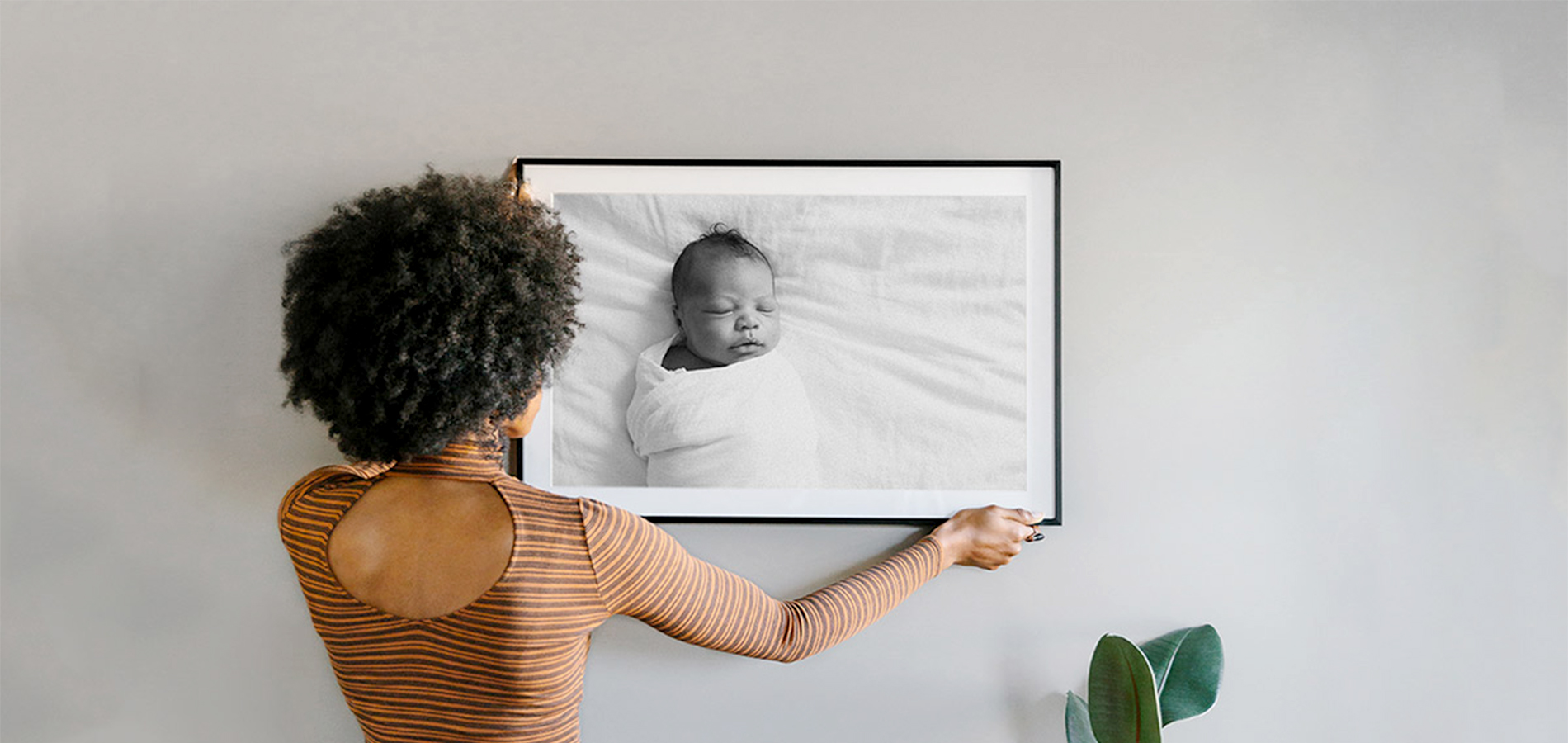 Woman hanging photo of newborn child on wall after choosing from different types of picture frame