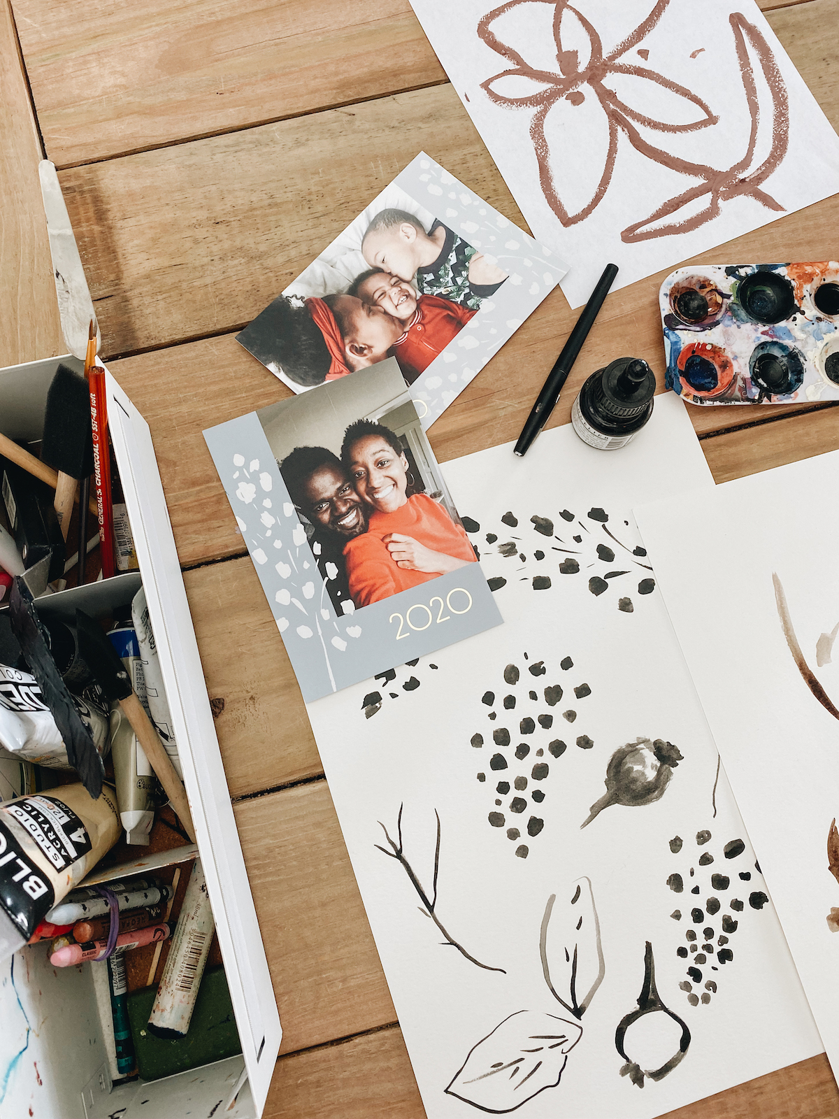 Holiday cards and drawings spread out on a studio table with art supplies