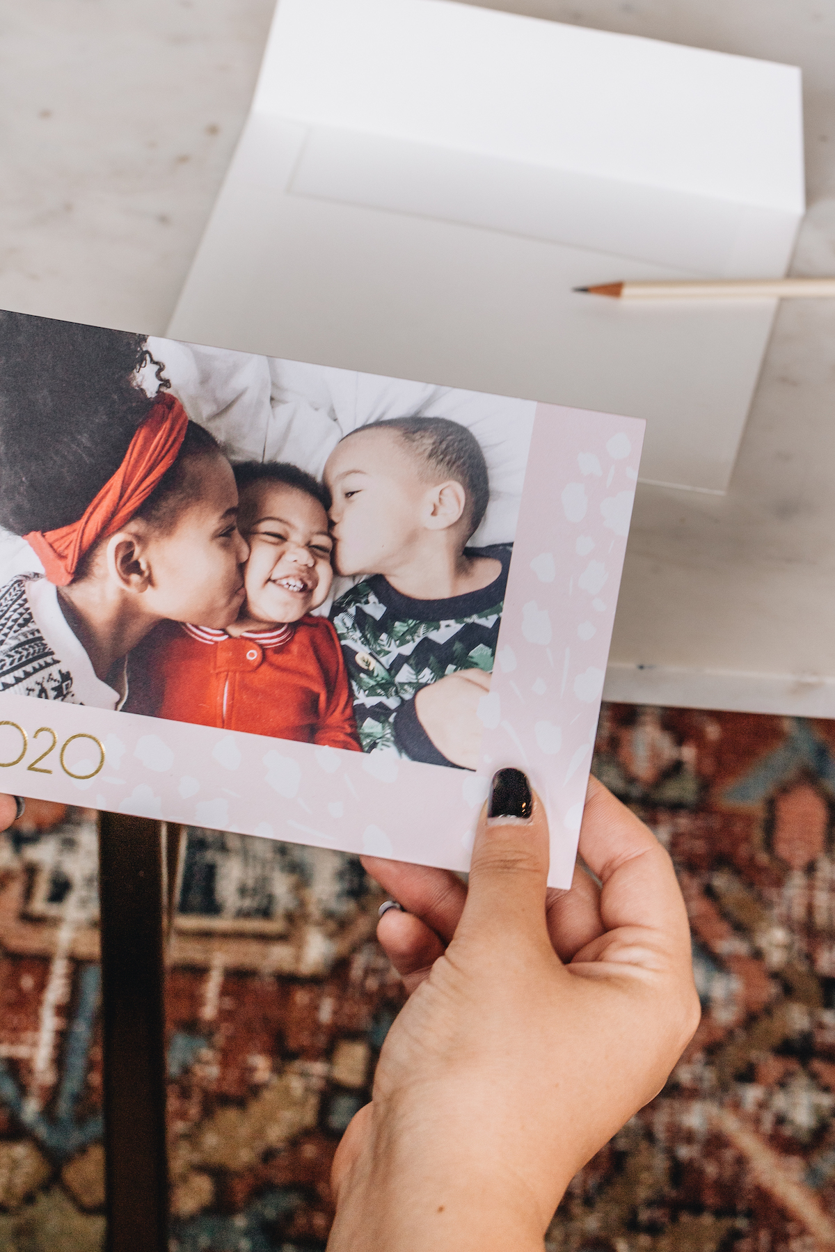 Hands holding up holiday card with trio of children in card image