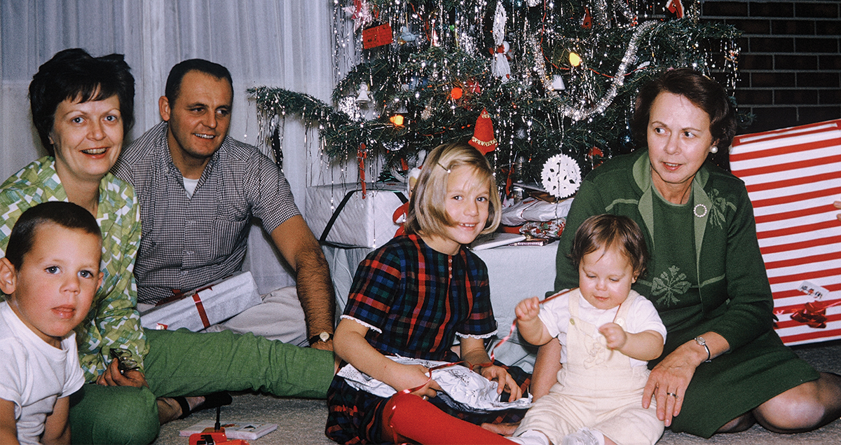 Vintage photo of family opening gifts by tree