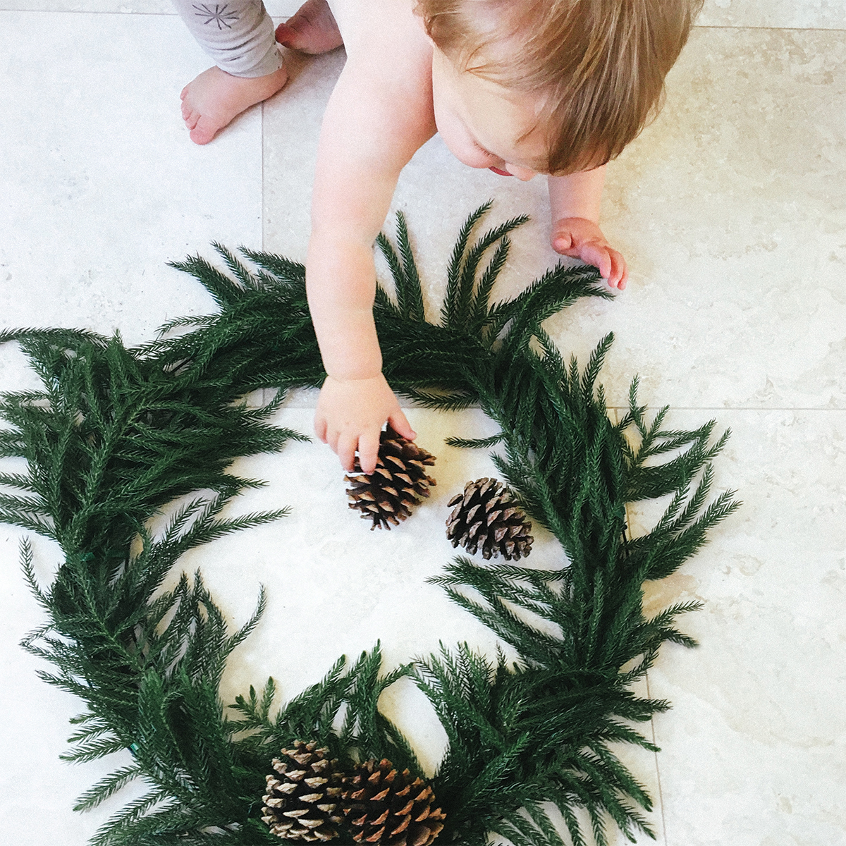 Toddler placing pinecone on homemade wreath