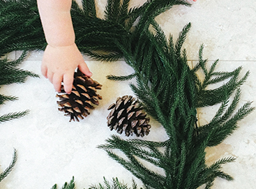 Child's hand placing pinecone on wreath