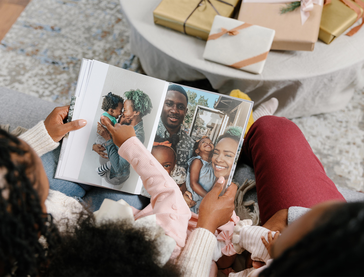 Mother and daughter flipping through pages of hardcover photo book on Christmas morning