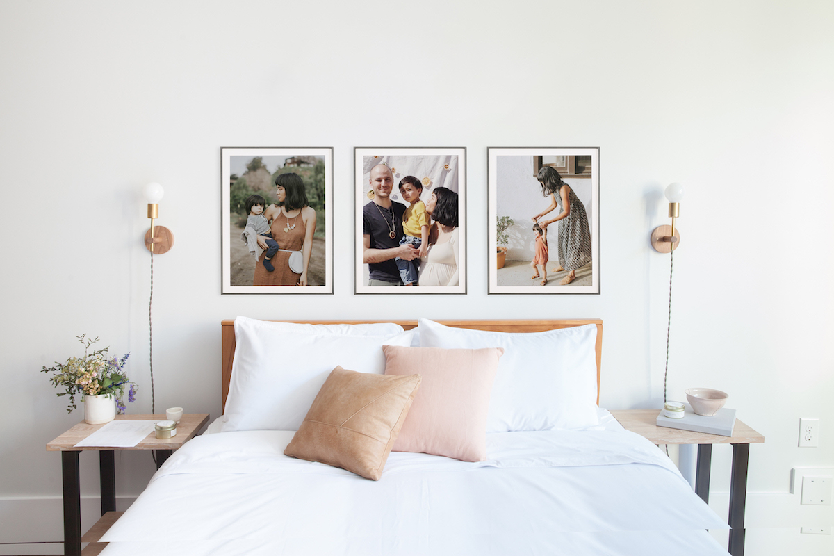 Three large family photos hung up side by side above bed