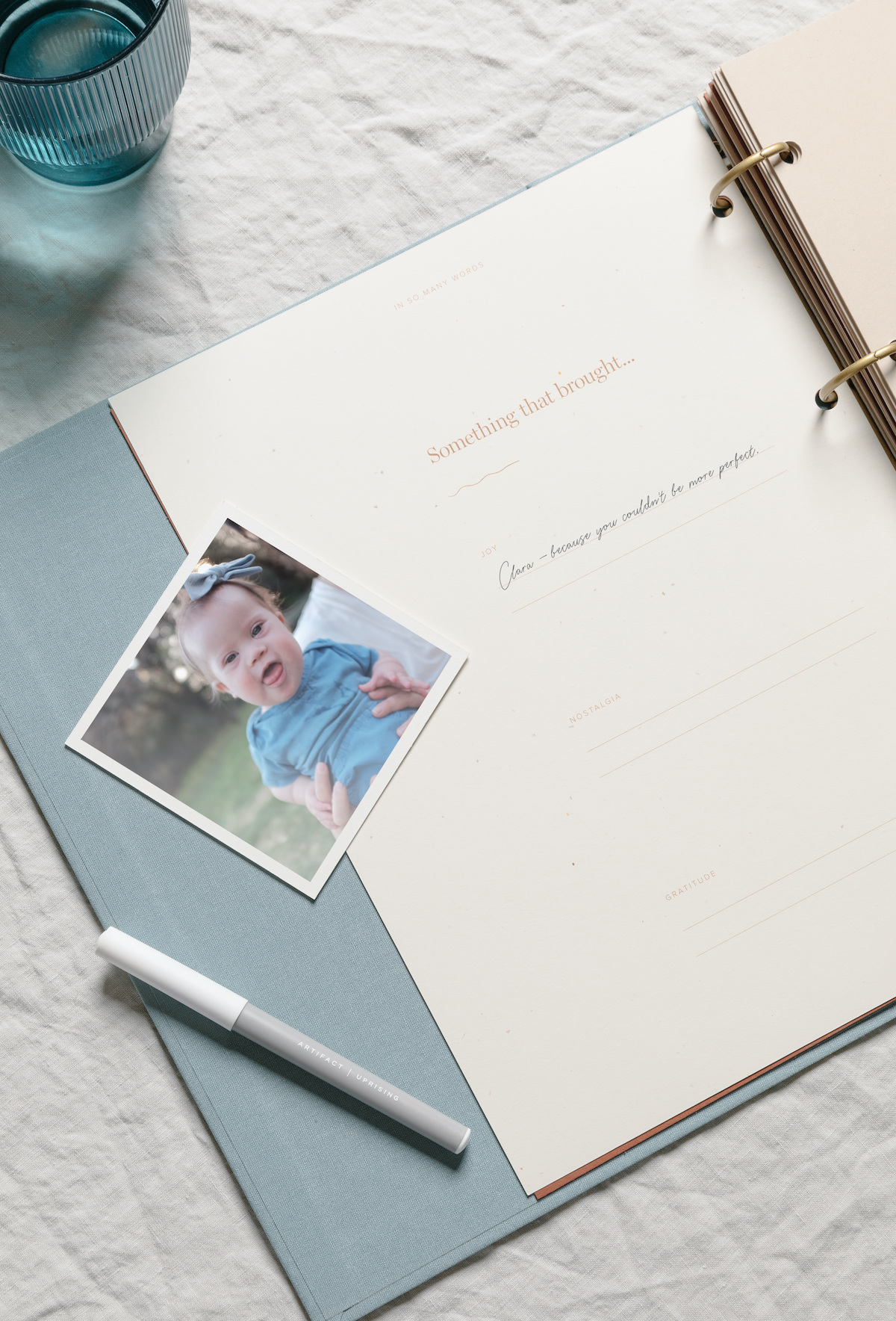 Photo of baby girl next to open scrapbook with writing inside