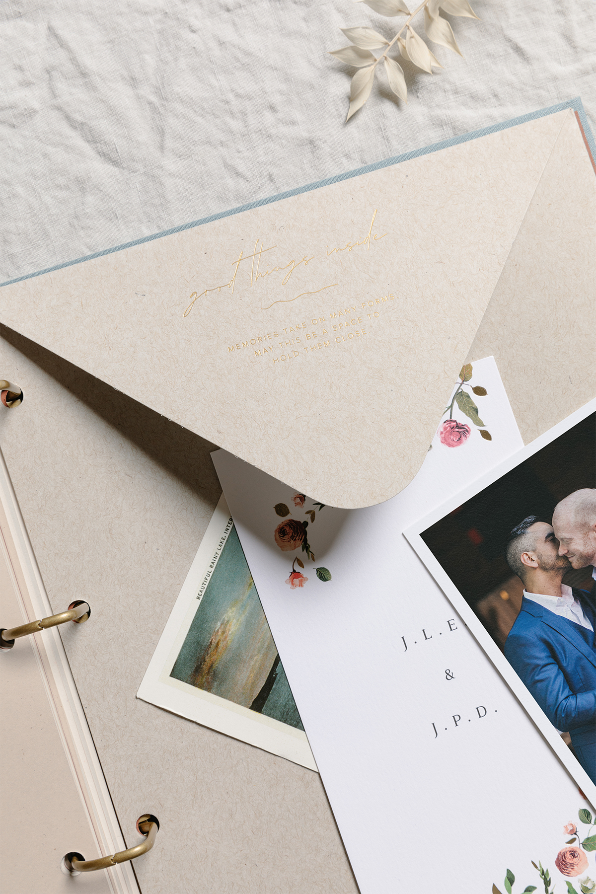 Large envelope inside of scrapbook with wedding invitations on top