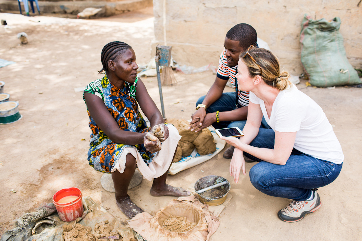 Becky and an Adventure Project volunteer speak with a clean cookstove entrepreneur in Tanzania