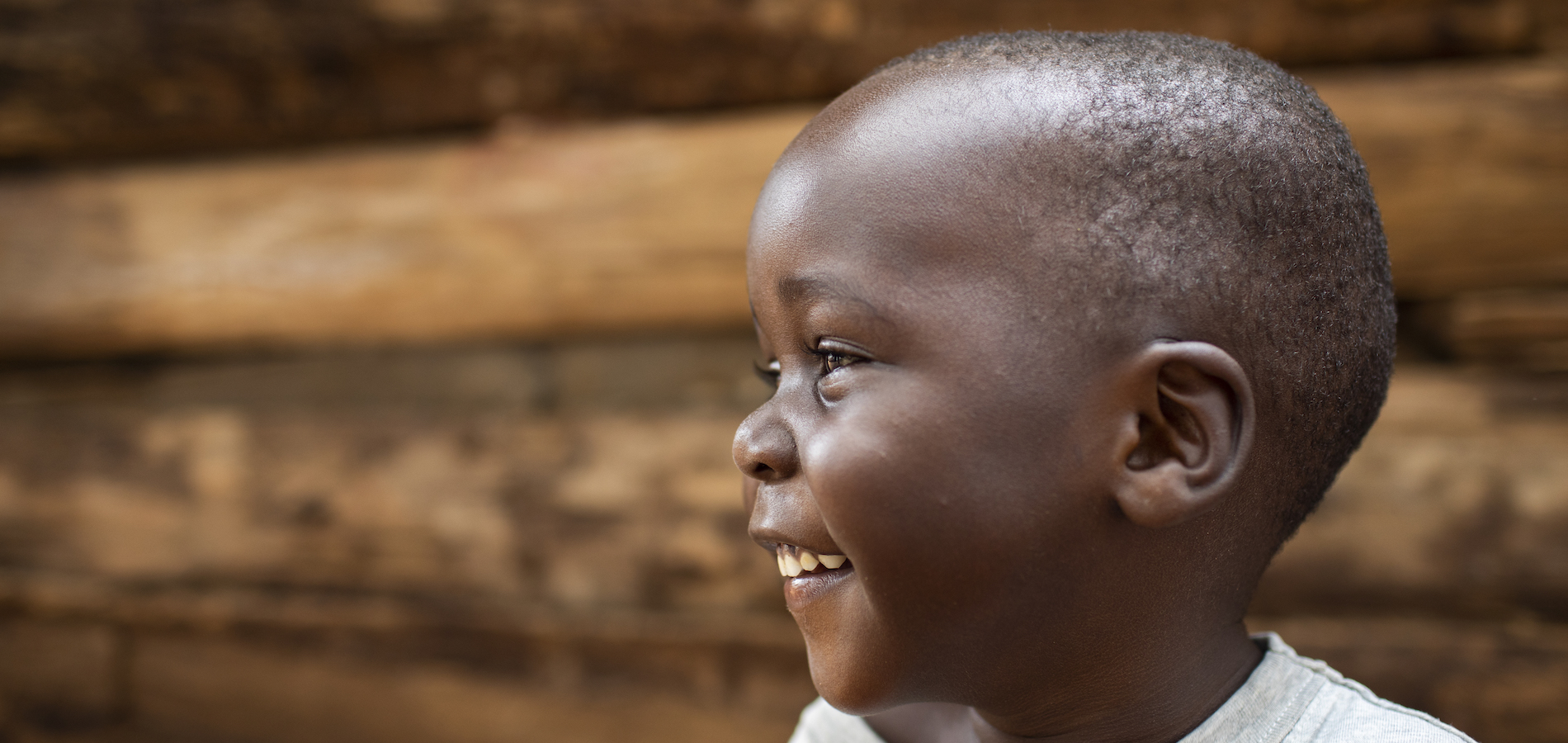 Close up of a little boy smiling with his head turned to the side