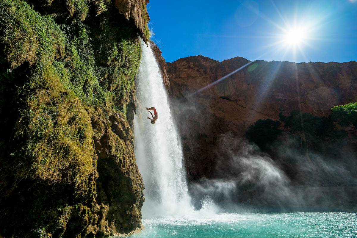 Man cliff diving next to waterfall in tropical setting