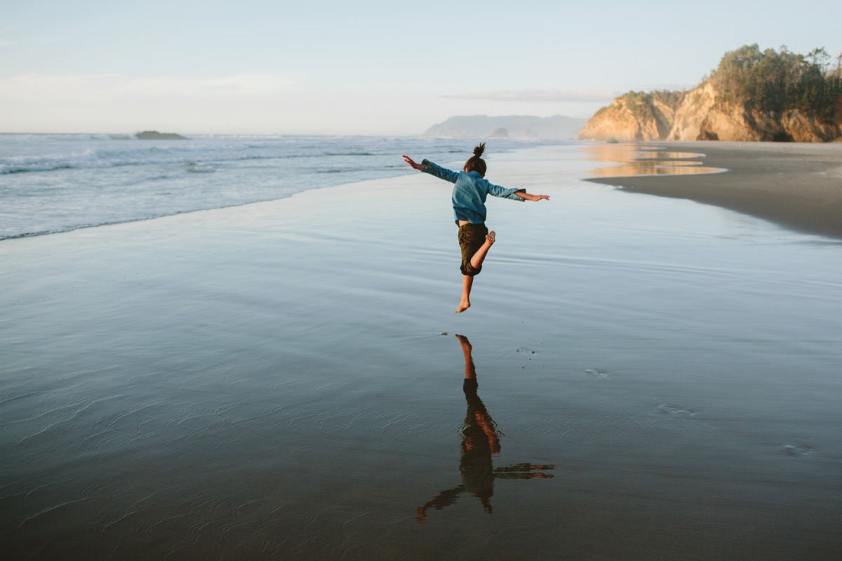 photo of child running and jumping along the coast