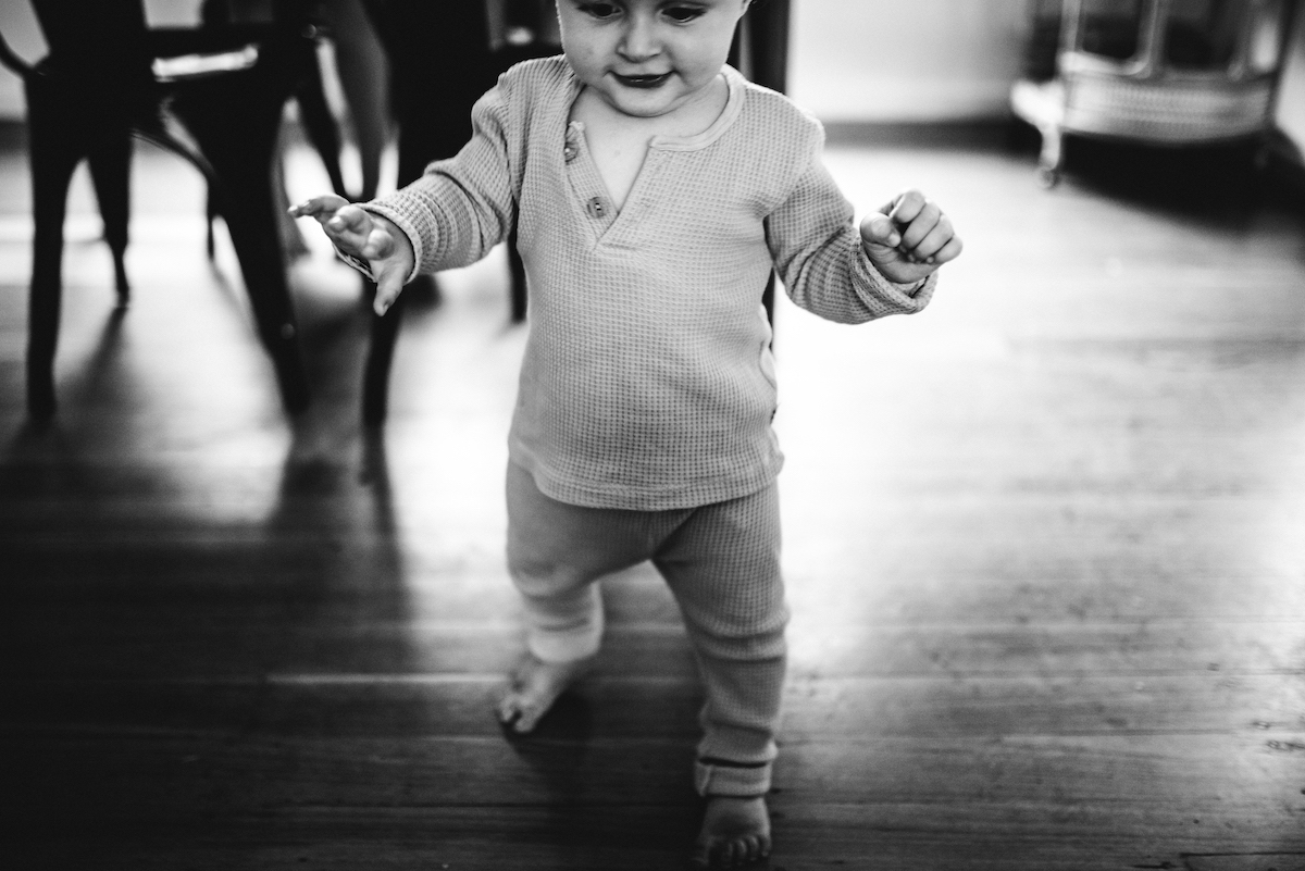 Black and white photo of baby taking first steps