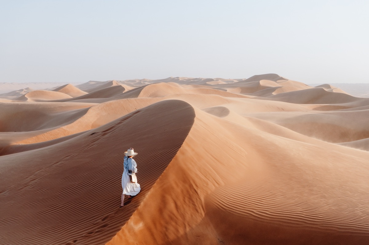 Woman standing atop a sand dune peering out into the desert in Oman