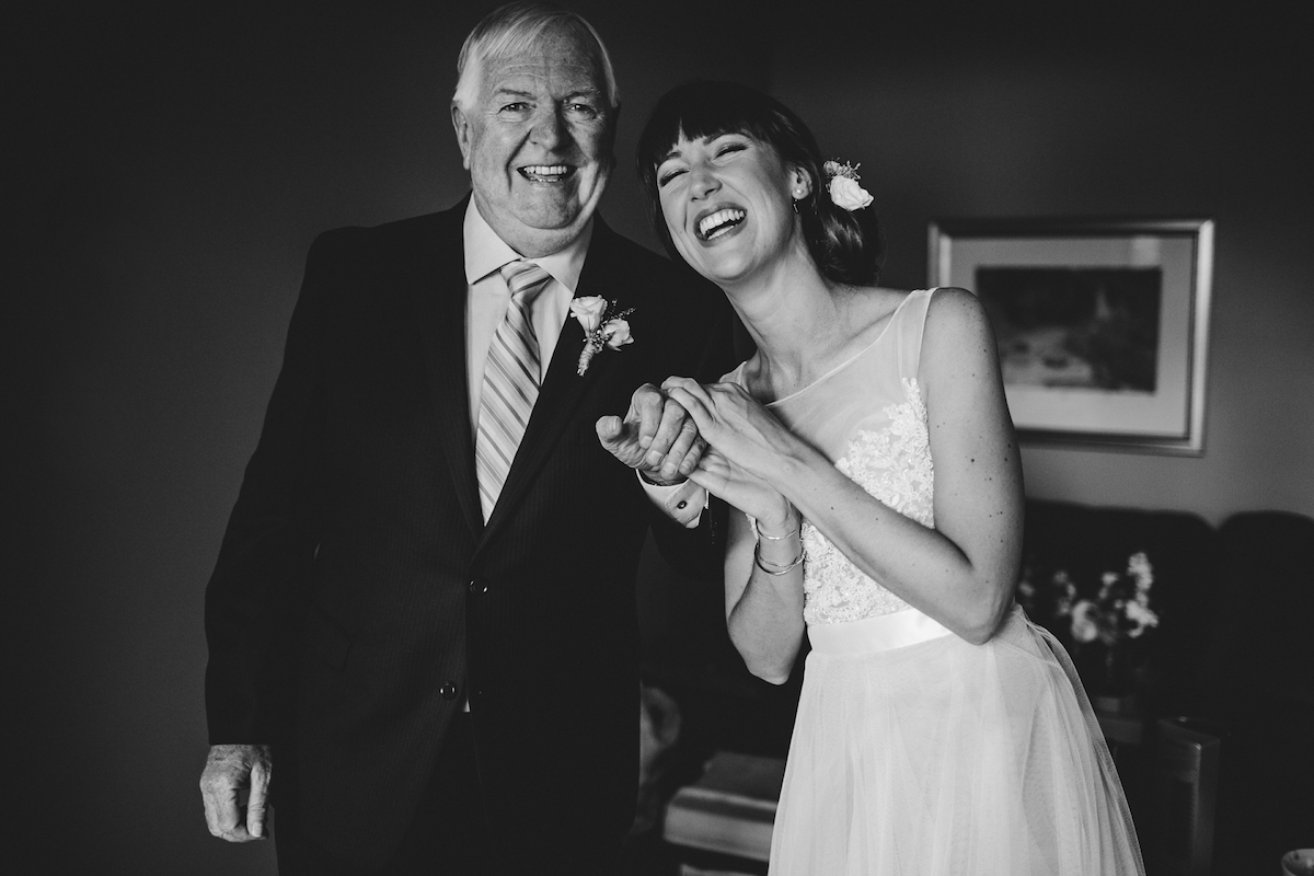 Black and white photo of laughing bride with father