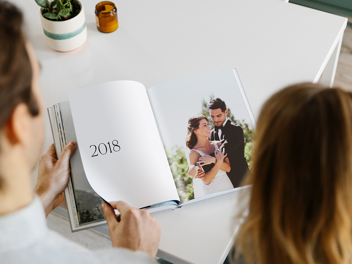 Hardcover Photo Book opened up to spread with 2018 on the left page and a wedding photo of a couple on the right page