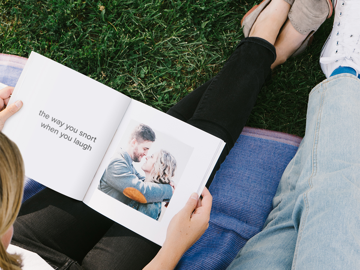 Couple flipping through Softcover Photo Book opened to photo of laughing couple