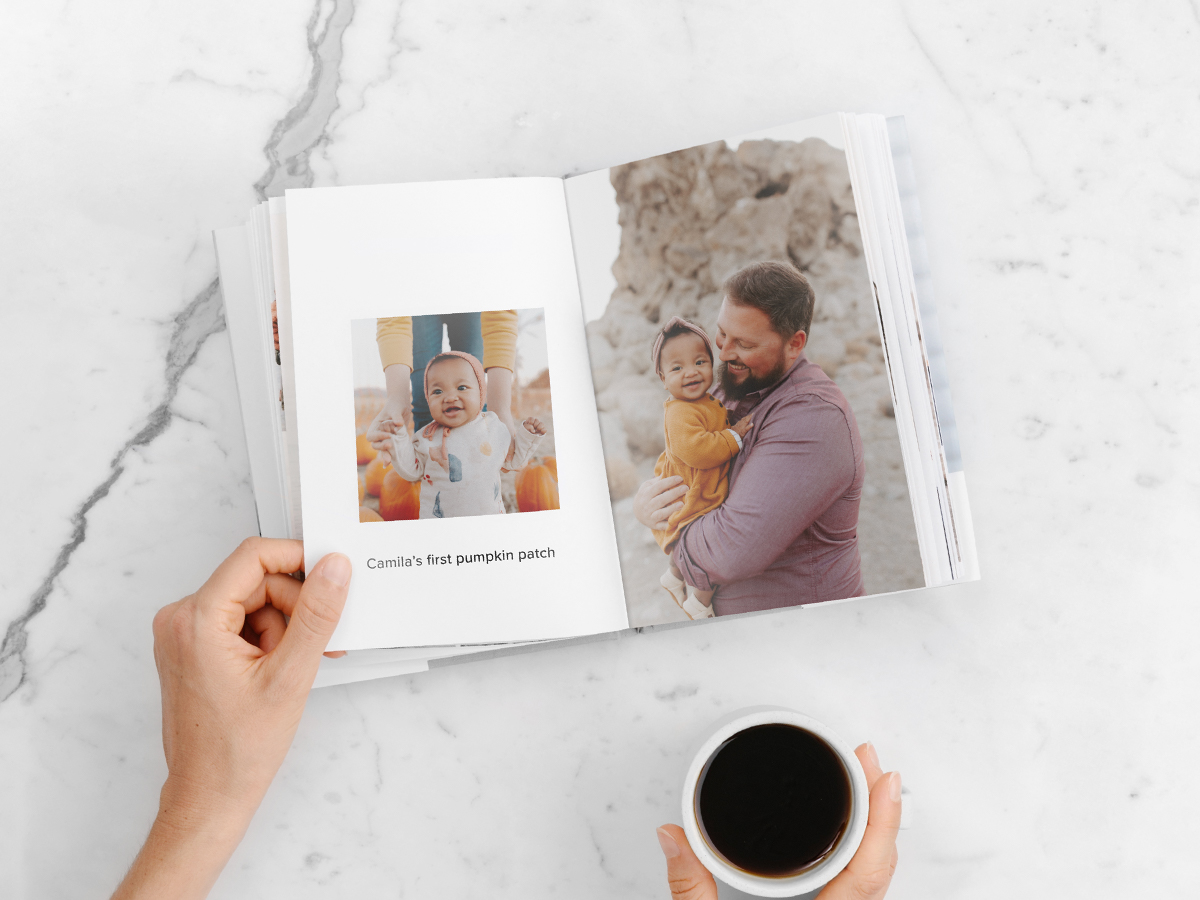 Hardcover photo book opened to photo of baby in pumpkin patch