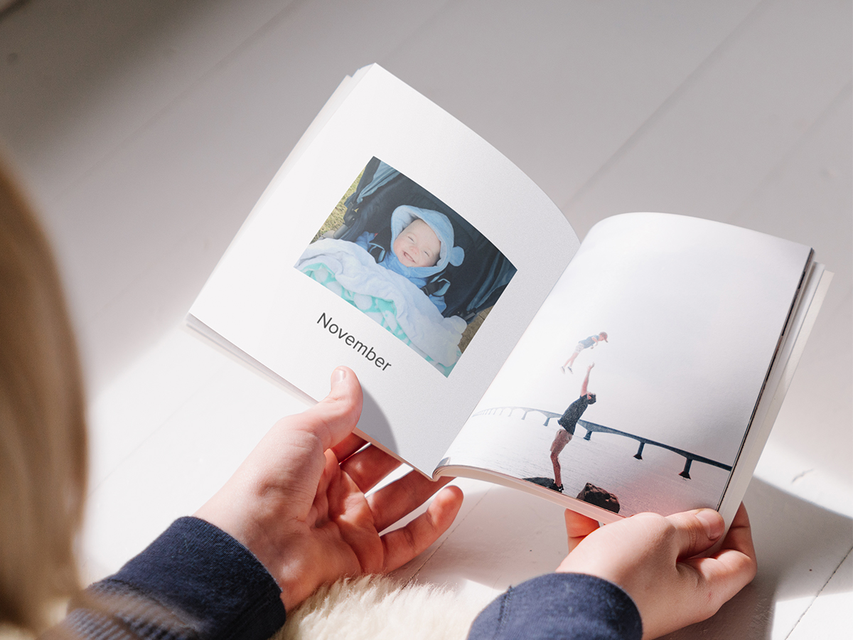 Softcover Photo Book opened to page marked November featuring baby photo