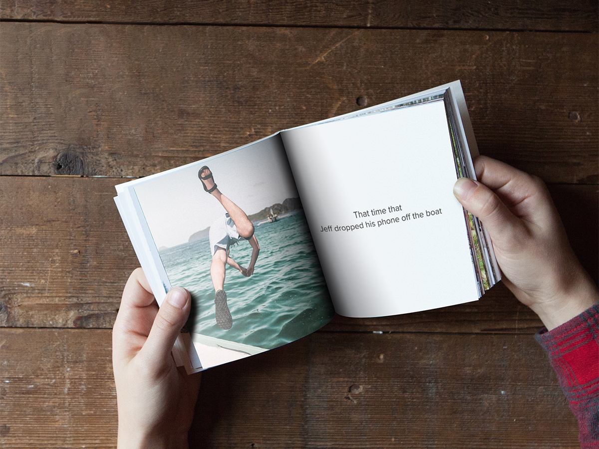 Softcover photo book opened up to a picture of a man diving into water off of a boat