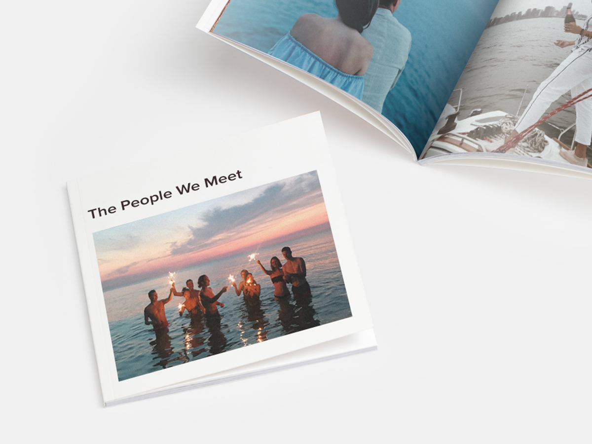 Softcover photo book titled the people we meet with an image of a group of people standing in the ocean