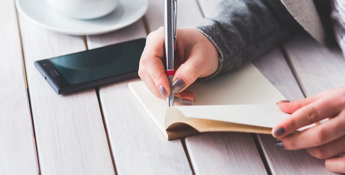 Woman's hand writing in journal with pen