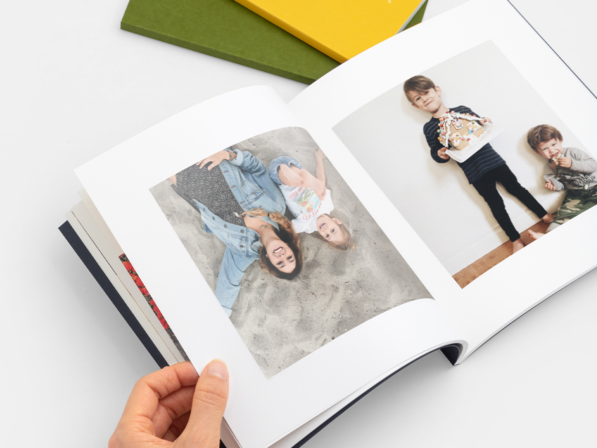 Photo book opened to images of children with gingerbread house