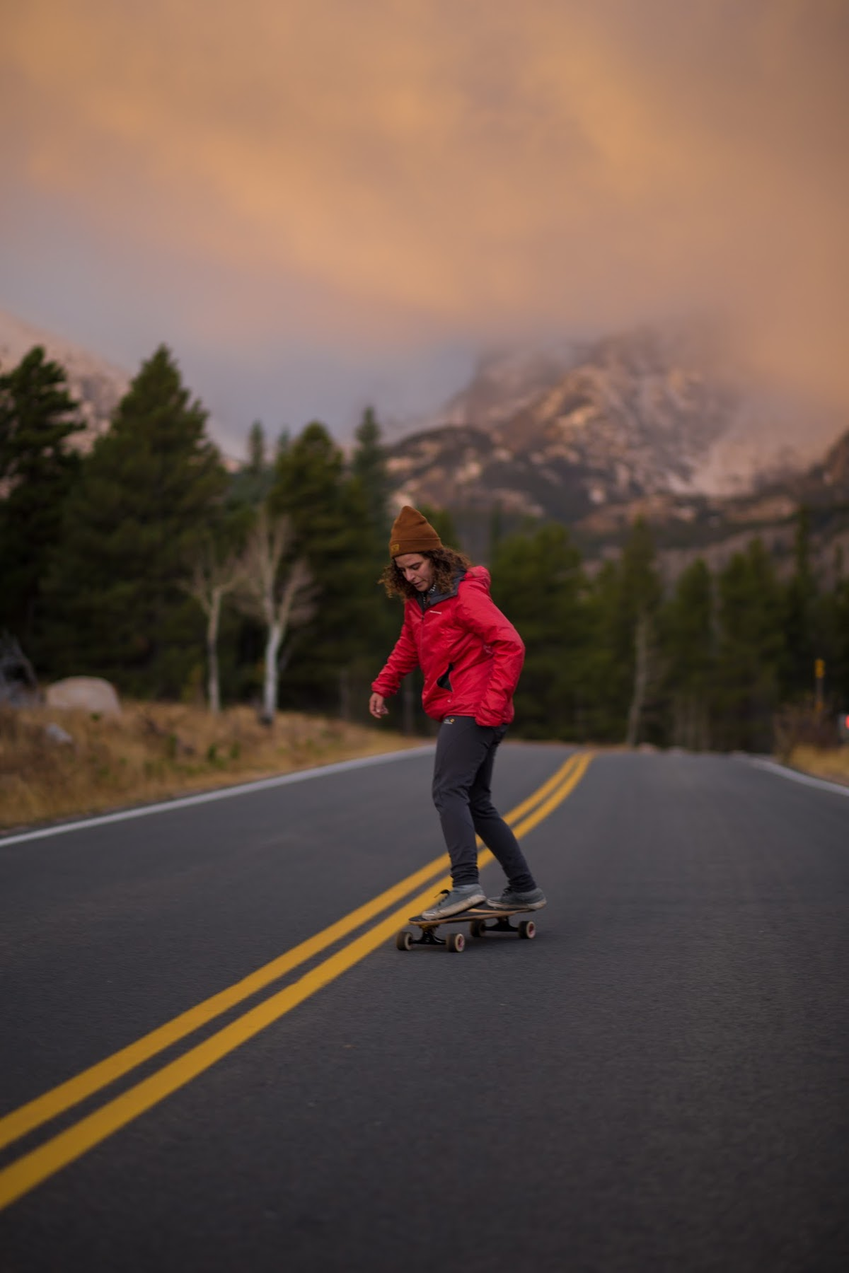 Skateboarder riding downhill on mountain road with snowy peaks in the background