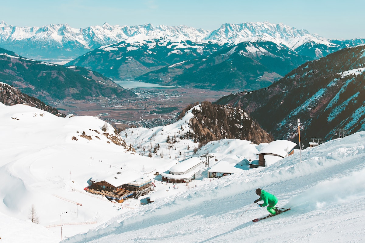Skier riding downhill with snowy peaks in the background