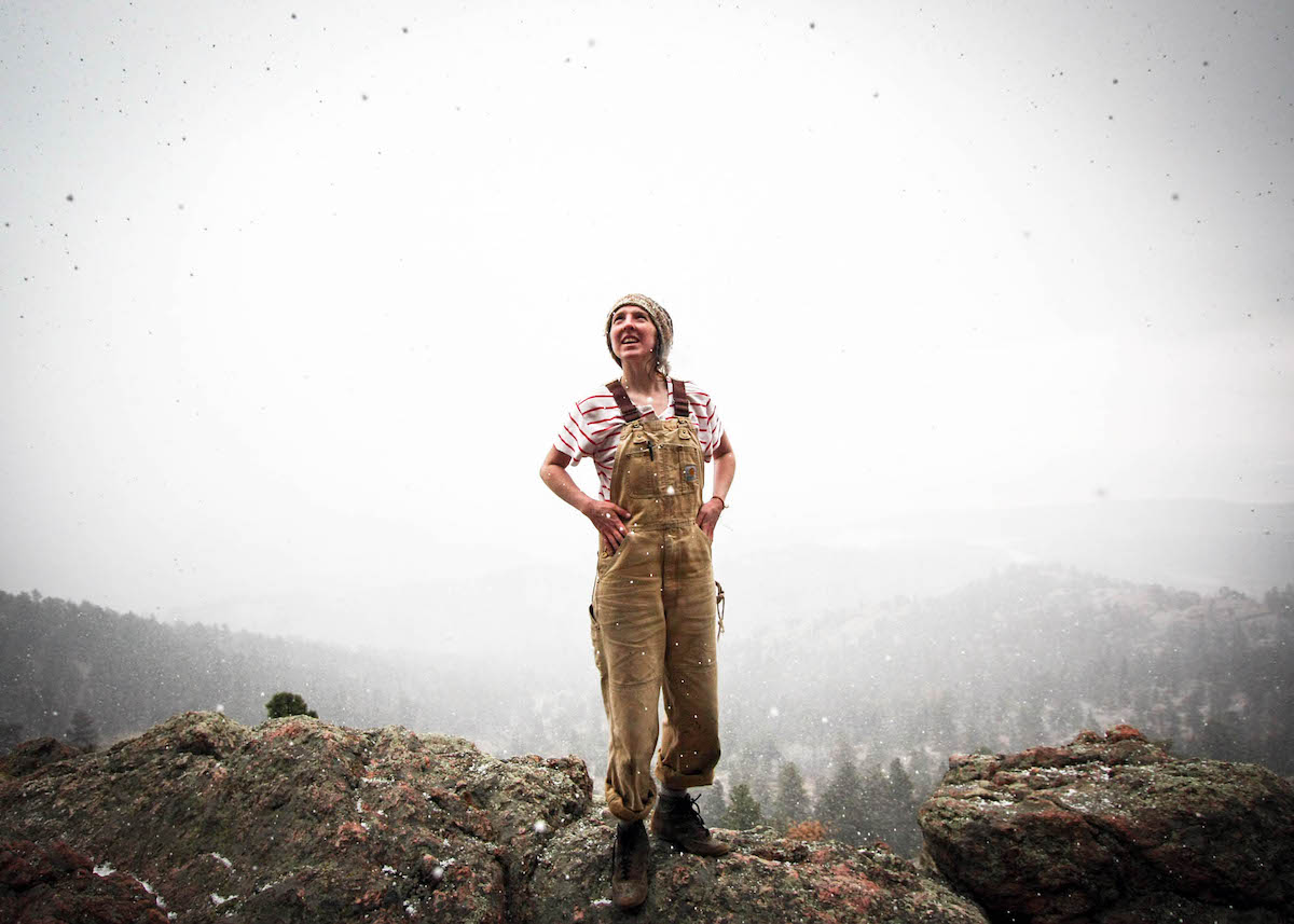 Girl in overalls looking up at the snow set against a mountainous winter background