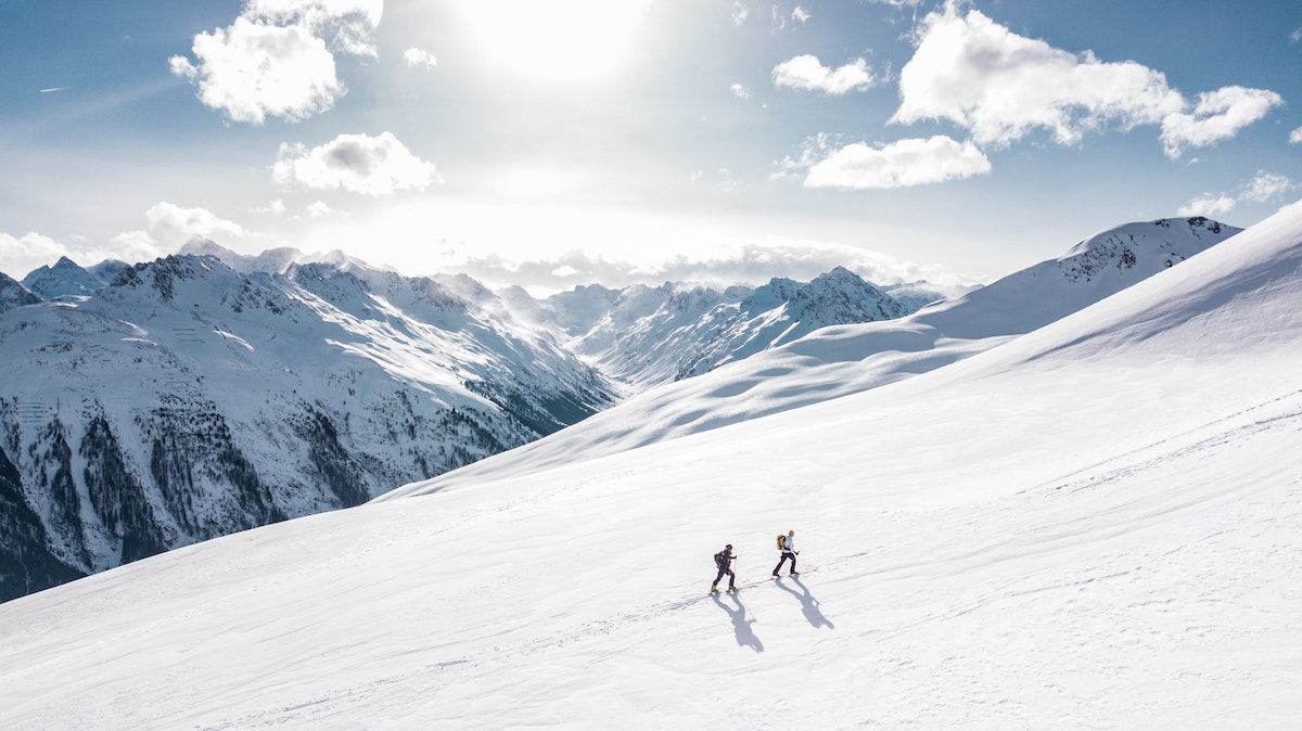Two hikers working their way up a snowy mountain with peaks in the background