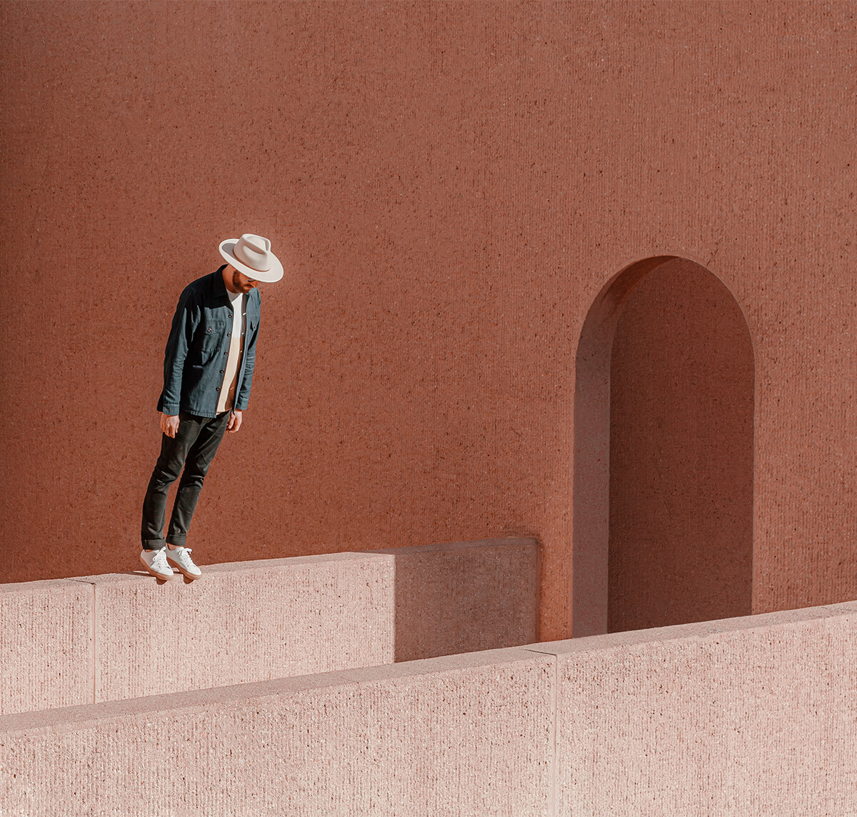Optical illusion of man standing on ledge and leaning over