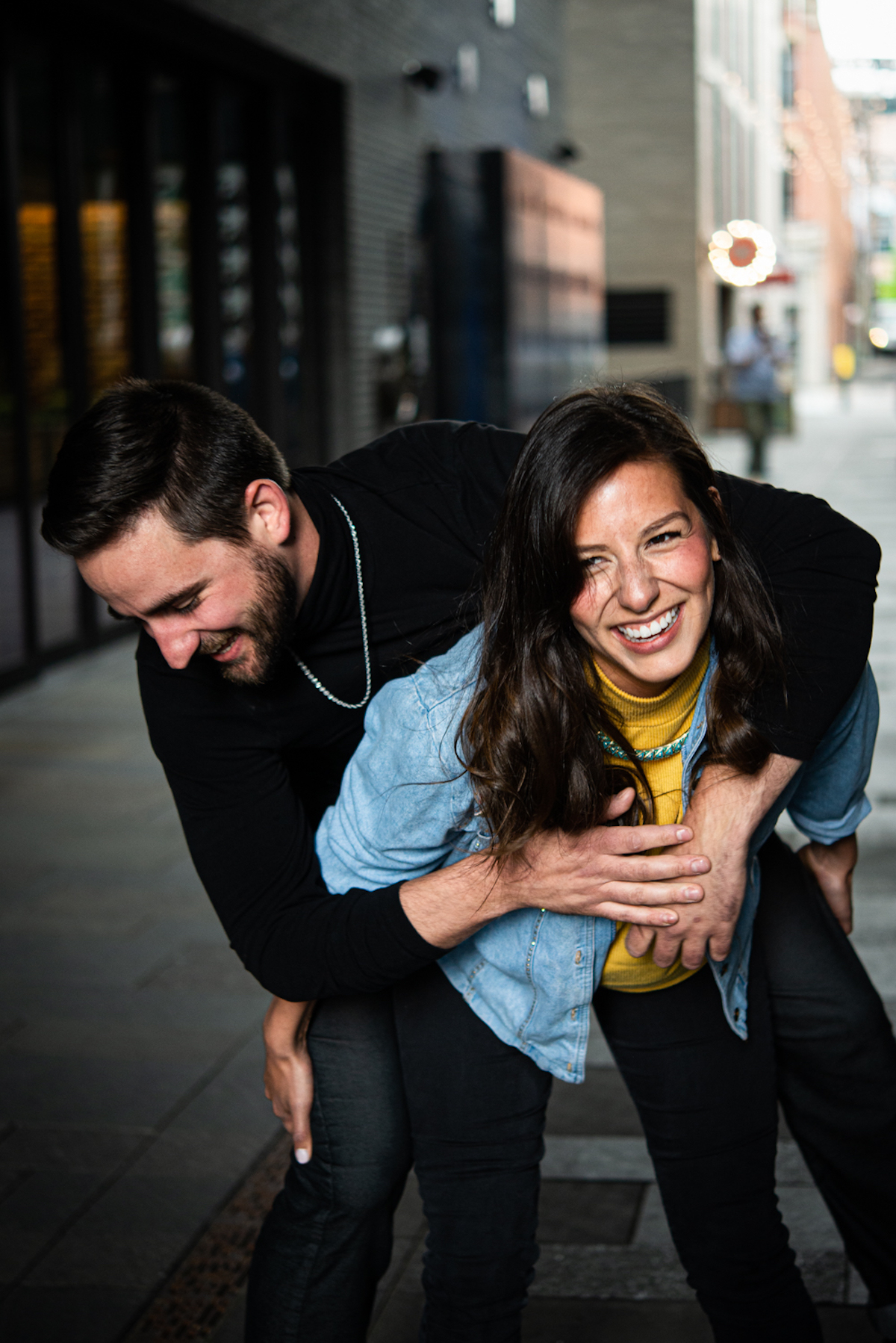 Young woman laughing as she tries to give boyfriend a piggyback ride
