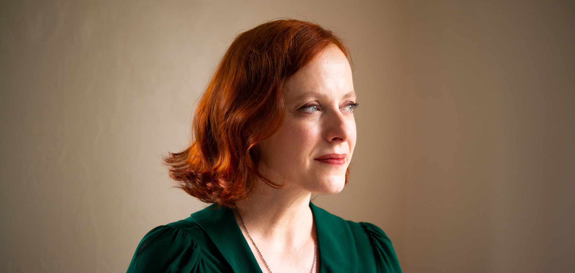 Headshot of redheaded woman set against beige backdrop
