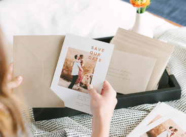 woman putting save the date card in envelope