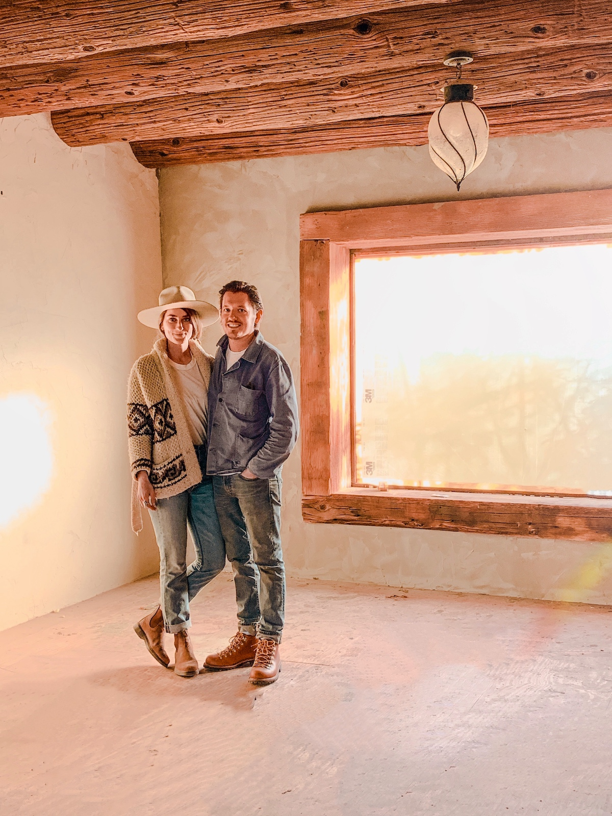 Sara and Rich stand in an empty room being renovated at the Joshua Tree House