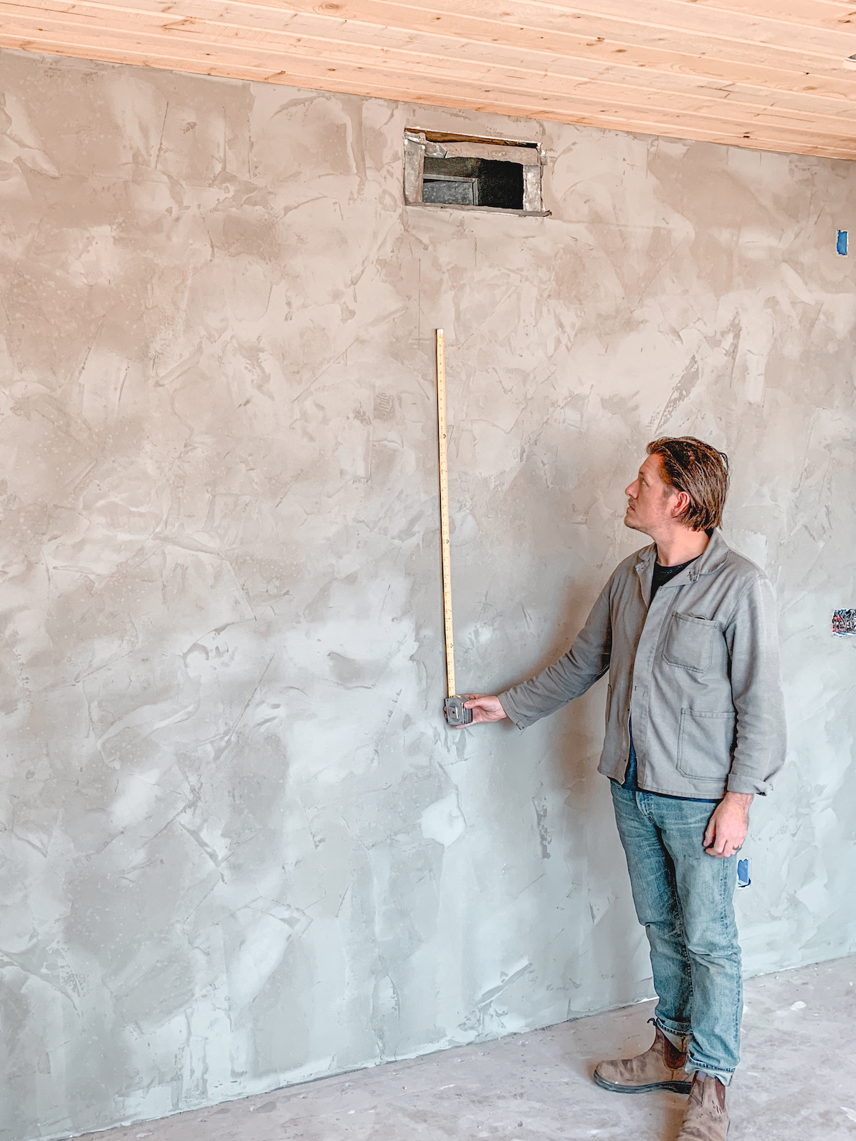 Rich holding a tape measurer up against the wall of a room in the middle of renovation