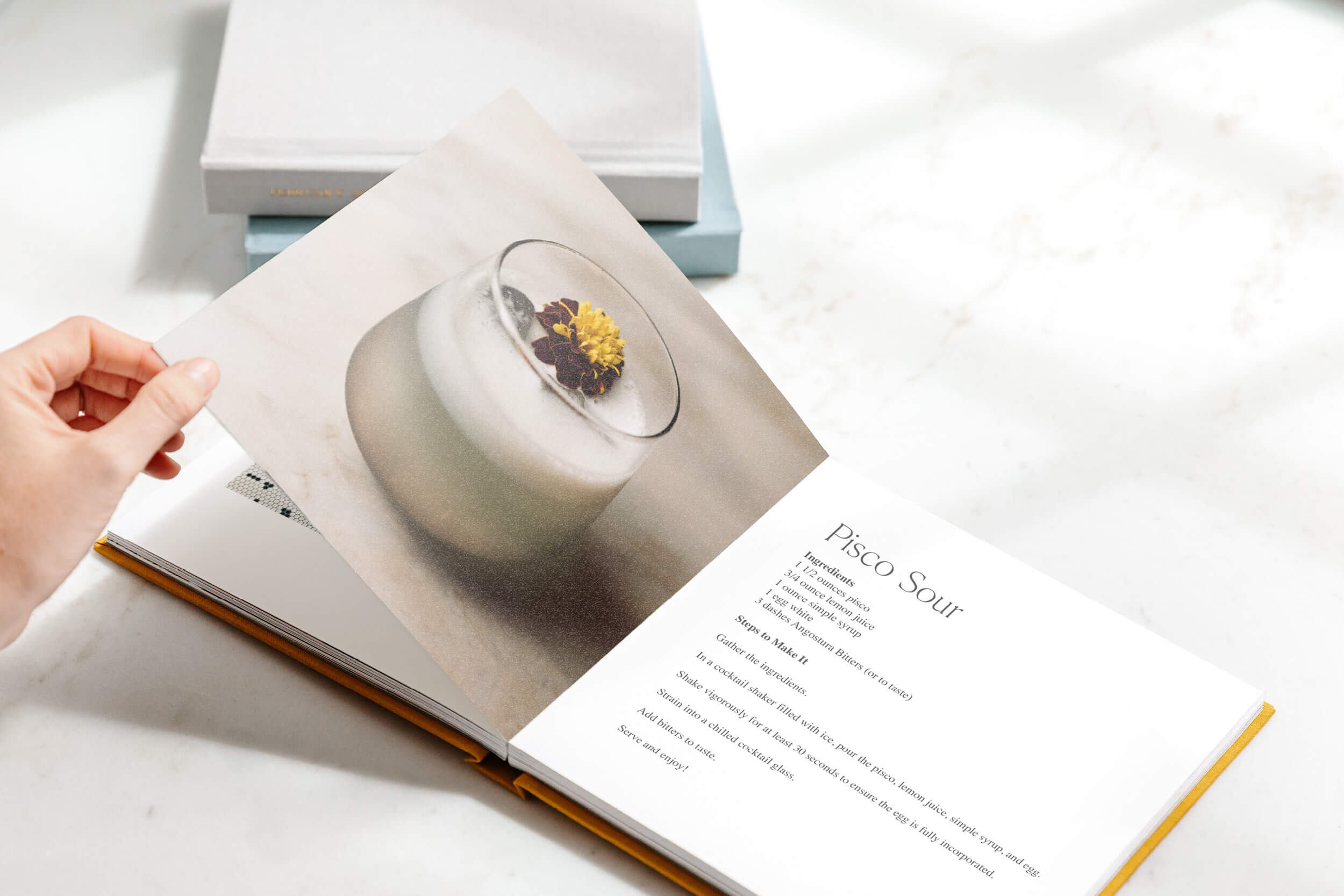 Cocktail book opened to recipe for a pisco sour