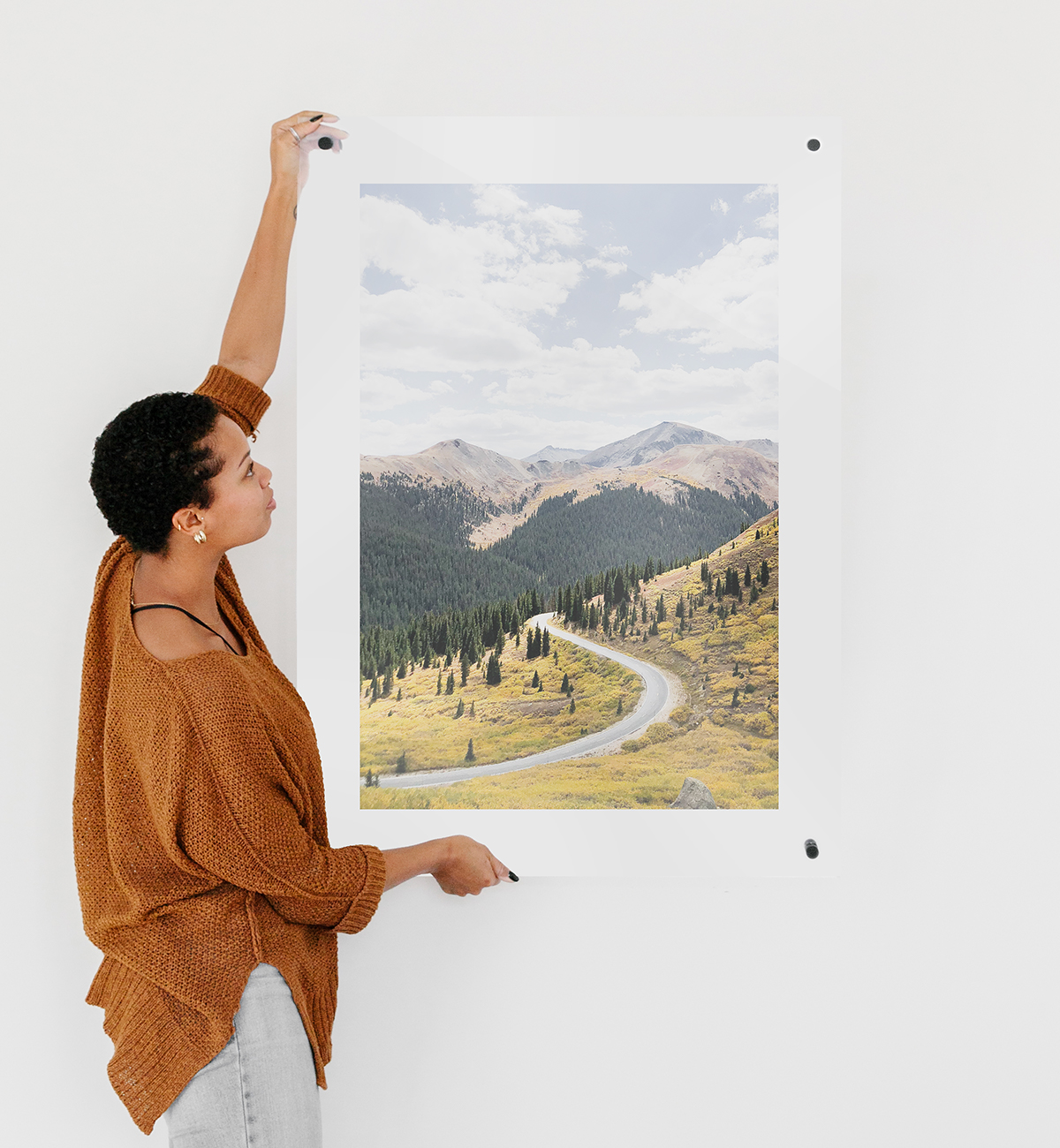 Woman hanging up floating frame featuring mountain landscape