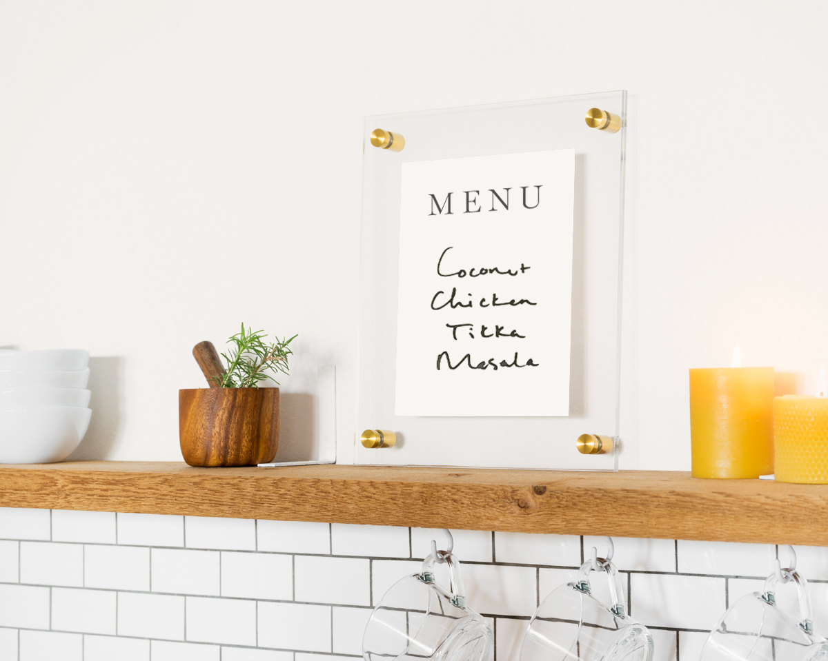Floating frame with menu written on it resting on mantel