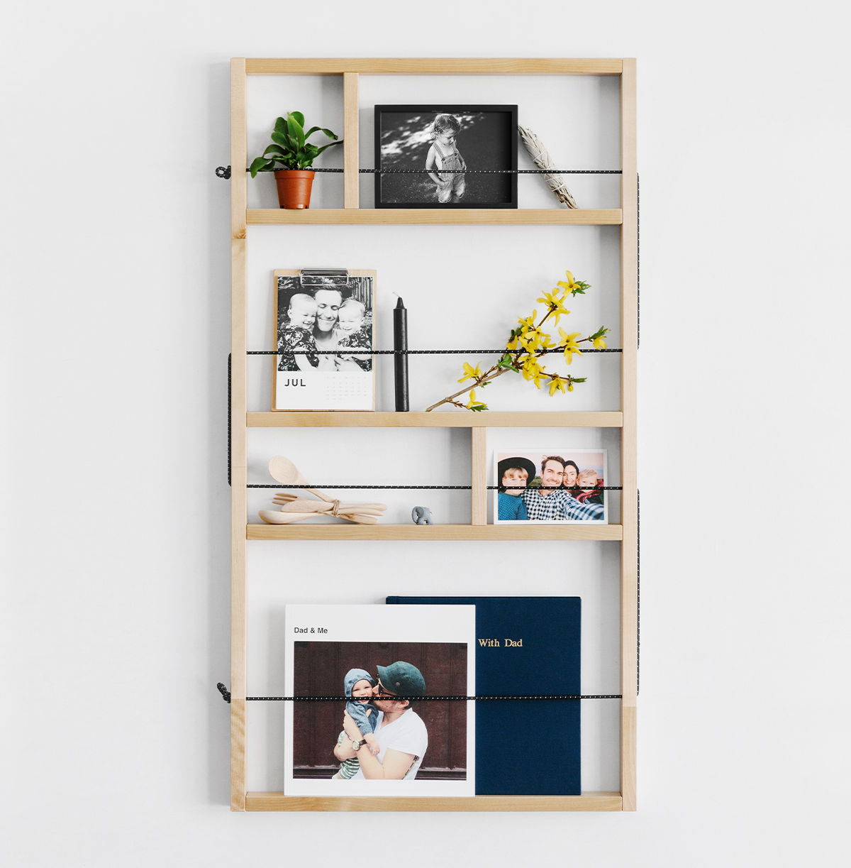 Wall-mounted shelf filled with photo-prints and other decor