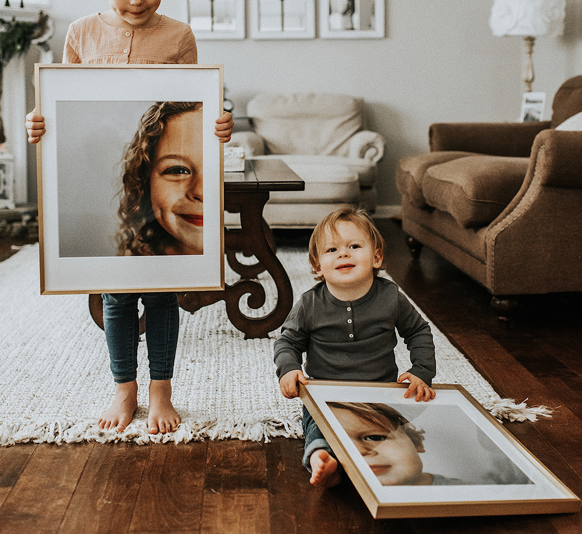 Two young siblings hold up enlarged and framed photos of themselves